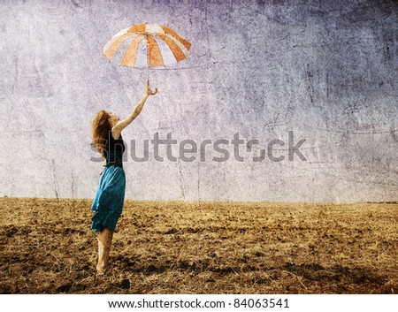 Redhead girl with umbrella at windy field. - stock photo