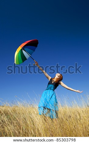 Redhead girl with umbrella at windy grass meadow. - stock photo