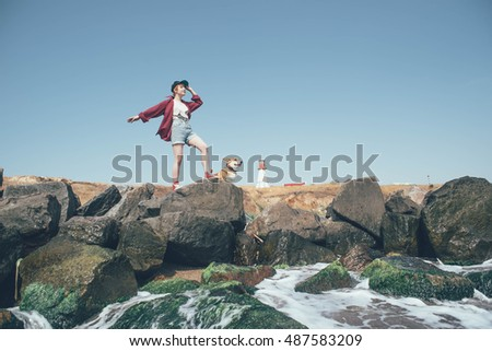 redhead girl with welsh corgi dog on the seaside near the lighthouse. Travel concept