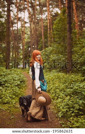 Redhead hippie walks in summer forest and playing with the dog. Young woman with long hair in a long skirt and blouse in Boho style. Photo of romantic girl in national dress. - stock photo