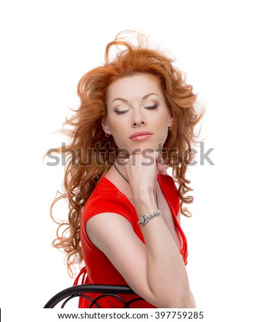 Redhead in a red dress in the chair with eyes closed.