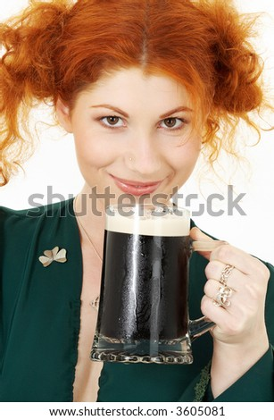 redhead in green dress with a mug of irish stout beer - stock photo