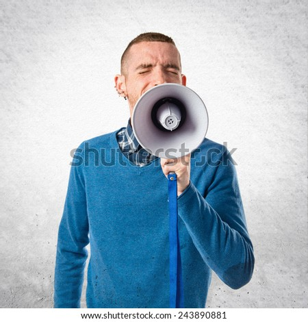 Redhead man shouting by megaphone over textured background