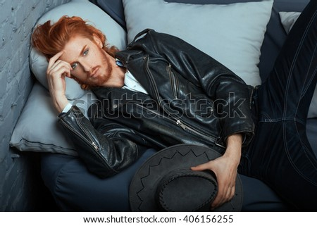 Redhead metrosexual man in casual style, lies on the couch. - stock photo
