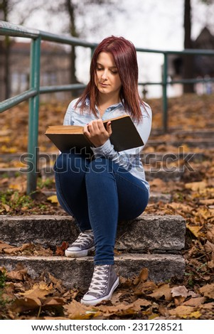 Redhead student girl standing,sitting,holding and reading a book in park