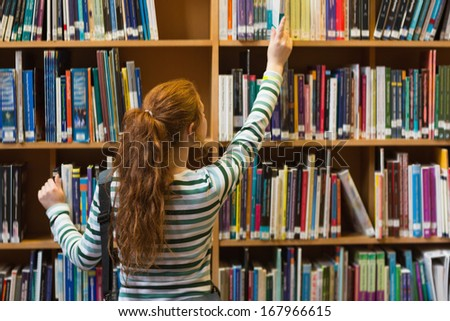 Redhead student taking book from top shelf in library at the university - stock photo