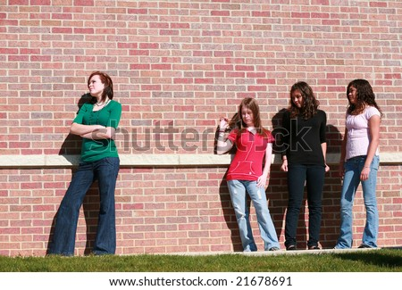 redhead teen girl standing out from a group of girls - stock photo