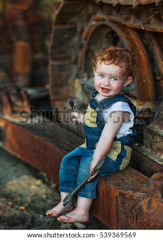 redhead toddler mechanic and abandoned old tractor, little boy with a wrench in hand on a background of rusty tractor, builder, worker, joke, transportation