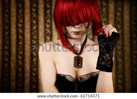 Redhead vampire with drop of blood, glamour background - stock photo