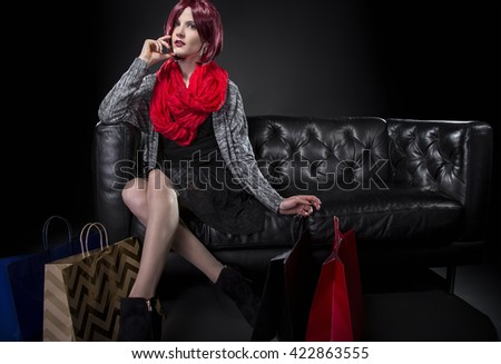 Redhead with Shopping Bags on a Black Leather Couch.  She is dressed in a red scarf. - stock photo