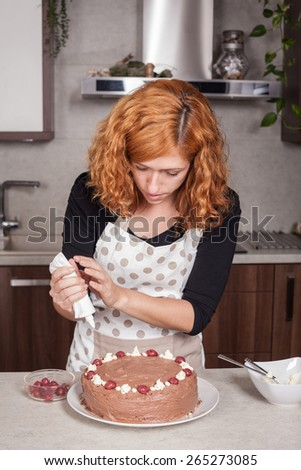 Redhead woman decorating homemade chocolate cake in the kitchen at home. - stock photo