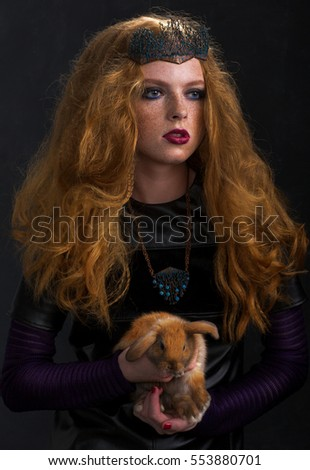 Redhead Woman holding little cute ginger rabbit. Fashion shooting