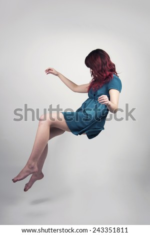 Redhead woman in a teal dress floating - stock photo