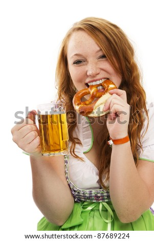 redhead woman in bavarian dress with beer eating pretzel on white background - stock photo