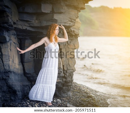 Redhead woman in summer white dress standing on beach and looking to the sea. Soft focus. With sunshine effect. Color toned image. - stock photo