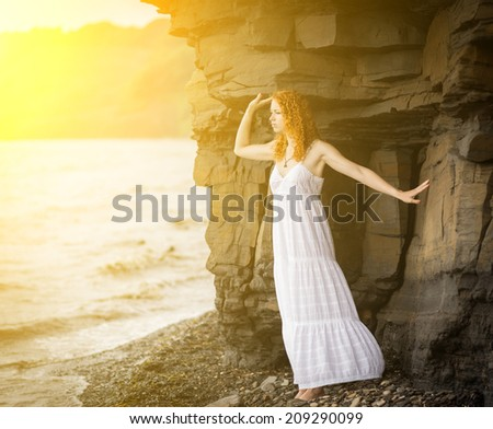 Redhead woman in white dress standing on beach and looking to the sea. Soft focus. With sunshine effect. Color toned image.  - stock photo