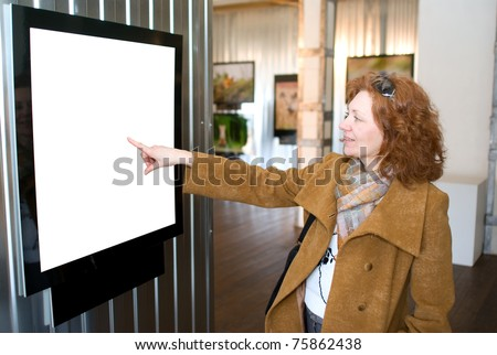 Redhead woman points to picture - stock photo