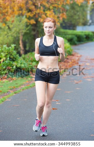 redhead woman running outside on a trail - stock photo