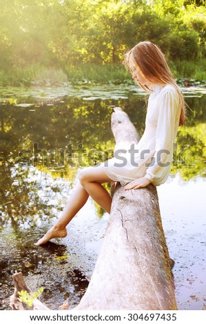Redhead woman sitting on a tree bark near river in wet blouse - stock photo