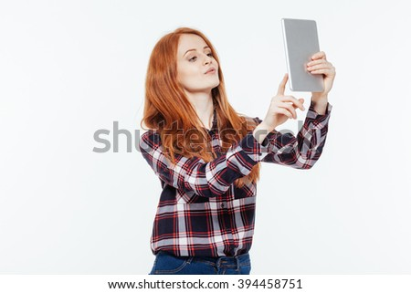 Redhead woman using tablet computer isolated on a white background - stock photo