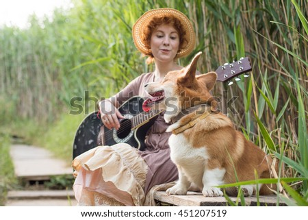redhead woman with guitar and corgi dog in countryside