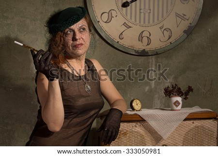 Redhead women in black veil with mouthpiece near the clock.  - stock photo
