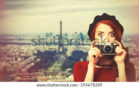Redhead women with scarf and vintage camera on Parisian background - stock photo
