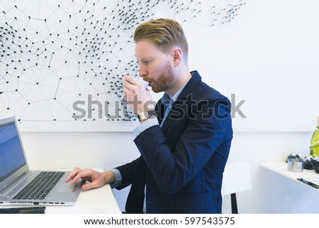 Redhead young business man hands doing something on laptop or notebook and drinking cofee. Modern office interior. Working people concept.