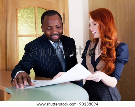 Redhead young business woman and black american business man smiling - stock photo