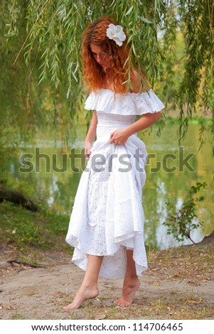 Redhead young, woman coming out of the river.