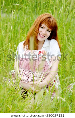 redhead young woman sitting in high grass