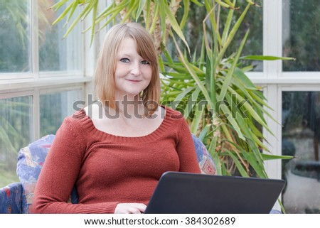 Redhead young woman with notebook is dressed in a brown sweater is sitting on the sofa in conservatory and she is looking at the camera. Green plant is in the background.