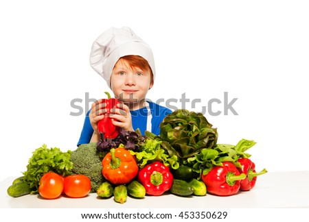 Redheaded boy in cook's uniform holding red pepper - stock photo