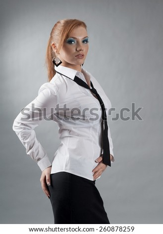 redheaded girl  in formal dress like a secretary with white shirt and tie