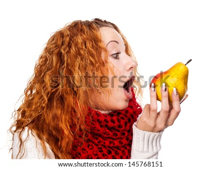 Redheaded girl wants to eat a pear isolated on white