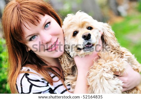 redheaded pretty girl hugging her dog (american cocker spaniel) on the meadow - stock photo