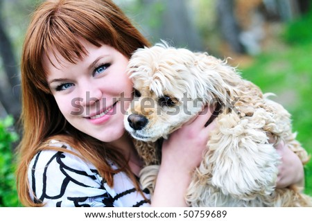 redheaded pretty girl hugging her dog on the meadow - stock photo