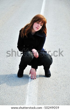 redheaded pretty girl sitting on the road - stock photo