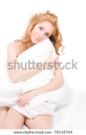 Redheaded woman holding pillow on white