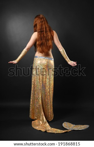 Redheaded woman is standing back. She is wearing a stage costume of the Golden Fish. - stock photo