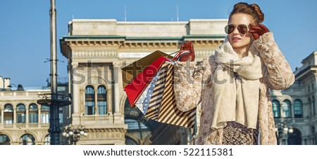 Rediscovering things everybody love in Milan. Full length portrait of modern traveller woman with shopping bags in Milan, Italy looking into the distance