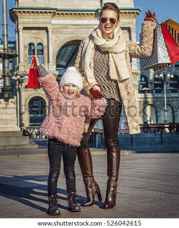 Rediscovering things everybody love in Milan. Full length portrait of smiling modern mother and daughter travellers with shopping bags near Galleria Vittorio Emanuele II in Milan, Italy rejoicing