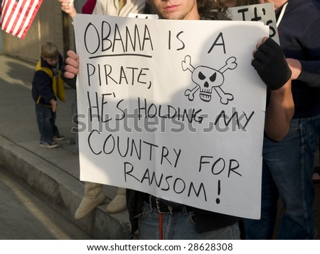 REDLANDS, CA - APRIL 15 : Protesters carry placards during tea party protest April 15, 2009 in Redlands, CA. The protest is a modern-day protest to the government's spending of billions of dollars. - stock photo