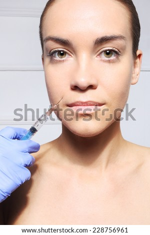Reduction of wrinkles, injection, nasal labial folds.Portrait of a white woman during surgery filling facial wrinkles  - stock photo
