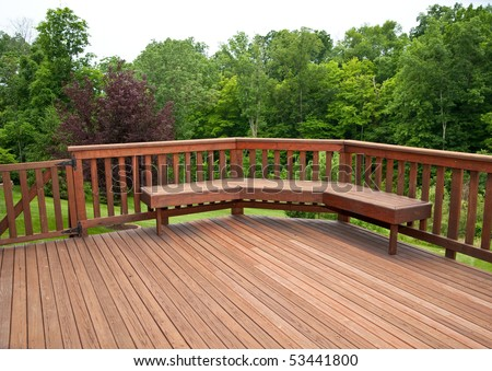Redwood stained deck boards with a bench seat overlooking the trees in the back yard of a residential home.