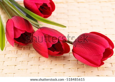 Reed fabric tulips on bamboo background.