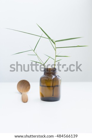 Reed in a jar and near wooden spoon on the white table. bamboo photo