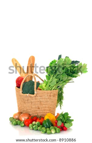 Reed shopping bag with fresh bio vegetables and french bread on reflective surface, studio shot, white background. - stock photo