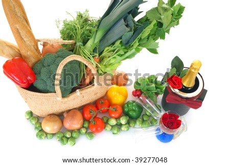 Reed shopping bag with fresh vegetables, bread, champagne on reflective surface, studio shot, white background. - stock photo
