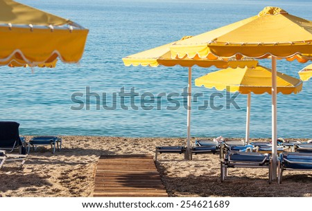 reed umbrella of the sea on a beach in the sun loungers - stock photo